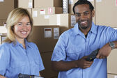 Male and female warehouse workers in warehouse — Stock Photo
