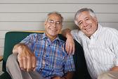 Deux hommes âgés assis et souriant — Photo