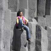 Woman sitting on rock ledge with eyes closed — Stock Photo