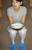 Asian woman eating cereal on stairs — ストック写真