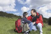 Asian father and son with backpacks outdoors — Stock Photo