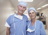 Senior male and female doctors wearing scrubs in hospital — Stock Photo