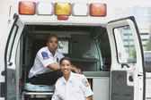 African female and male EMTs in ambulance — Stock Photo