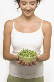 Young woman holding a bowl of sprouts — Stockfoto