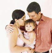 Couple kissing their baby girl — Stock Photo