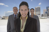 Businesswoman with co-workers in urban background — Stock Photo