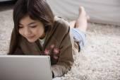 Young Hispanic girl lying on the floor with laptop — Stock Photo
