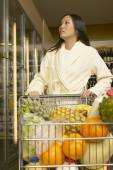 Asian woman at grocery store in bathrobe — Stock Photo