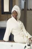 African American woman in bathroom wearing bathrobe — Stock Photo
