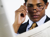Young businessman reading newspaper over glasses — Stock Photo