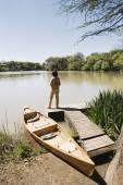 Woman standing on dock next to canoe — Stock Photo
