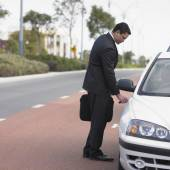 Businessman unlocking a car door — Stock Photo