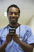 African male surgeon using electronic organizer — Stock Photo