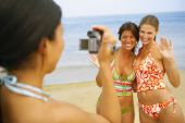 Woman video recording friends at beach — Stock Photo