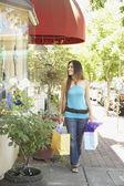 Hispanic woman on sidewalk holding shopping bags — Stock Photo