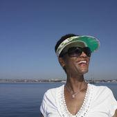 Senior African woman smiling next to water — Stock Photo