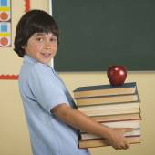 Boy carrying stack of books and apple in classroom — Stock Photo