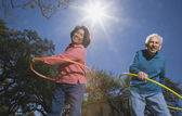 Senior couple with hula hoops — Stock Photo
