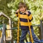 Hispanic boy standing on tire swing — Stock Photo #52066787