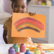 African American girl holding up painting — Stock Photo #52066799