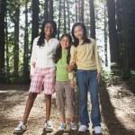 Multi-ethnic girls standing in woods — Stock Photo #52067661