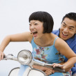 Asian couple riding motor scooter — Stock Photo #52067721