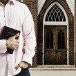 Mixed Race man holding the bible in front of church — Stock Photo #52067849