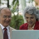 Senior Hispanic couple looking at laptop — Stock Photo #52068011