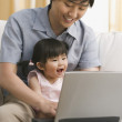 Asian father and baby daughter looking at laptop — Stock Photo #52068545
