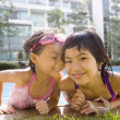 Asian sisters getting out of swimming pool — Stock Photo #52069727