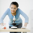 Mixed Race teenage girl using microscope — Stock Photo #52069941