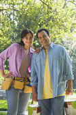Hispanic couple with tool belt and paint cans — Stock Photo