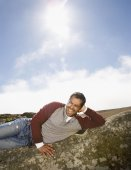Pacific Islander man laying on rock formation — Stock Photo