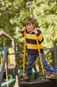 Hispanic boy standing on tire swing — Stock Photo