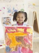 African girl holding painting — Stock Photo