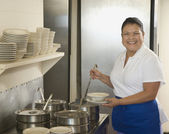 Hispanic waitress ladling soup — Stock Photo