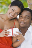 Multi-ethnic couple holding gift — Stock Photo