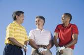Multi-ethnic men holding golf clubs — Stock Photo