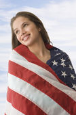 Teenaged girl wrapped in American flag — Stock Photo