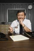 Senior Asian businessman at desk — Stock Photo