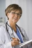 Hispanic female doctor writing on chart — Stock Photo