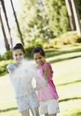 Hispanic sisters spraying hose — Stock Photo