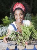 African American woman holding potted plants — Stock Photo