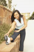Asian woman in running gear stretching — Stock Photo