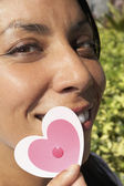 Hispanic woman holding cut-out hearts — Stockfoto