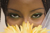 African woman with flower in front of face — Stock Photo