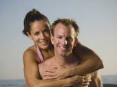 Multi-ethnic couple hugging at beach — Stock Photo