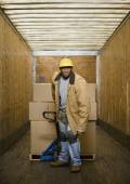 African warehouse worker pulling pallet in truck — Stock Photo