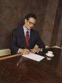 Hispanic businessman writing — Foto de Stock