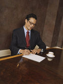 Hispanic businessman writing — Stock Photo